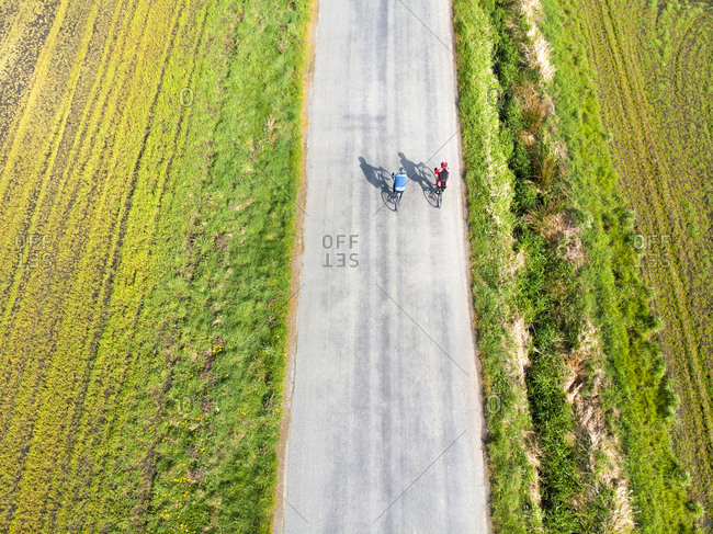 Two people cycling near farmland