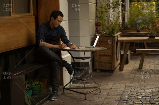 Businessman writing on diary with laptop on table at pavement cafe
