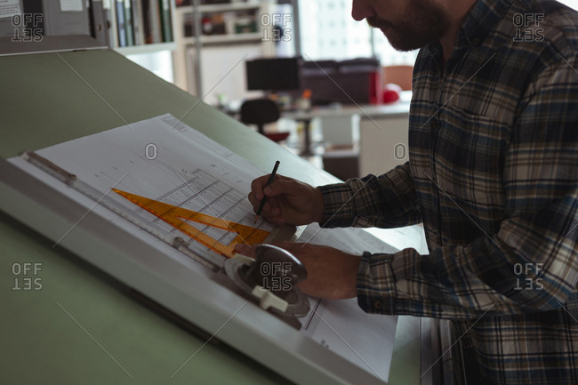 Architect working on blueprint on drafting table in the office