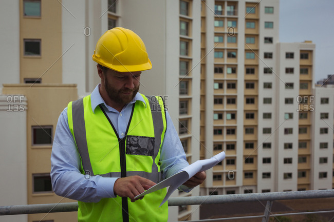 Architect checking documents on clipboard at site