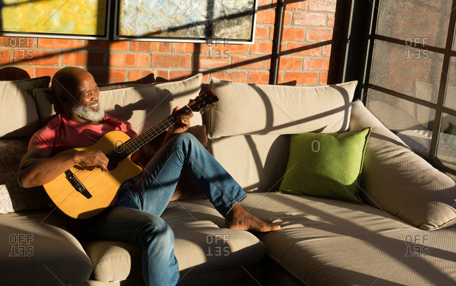 Active senior man playing guitar at home