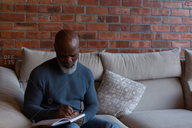 Senior man writing in a diary at home