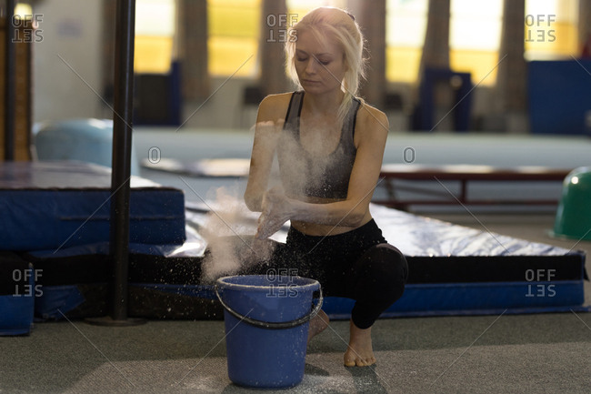 Sportswoman dusting her hands with chalk powder at fitness studio