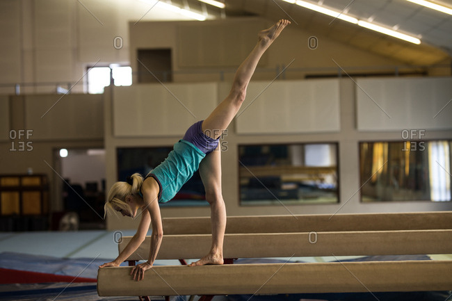 Female athletic balancing on wooden bar at fitness studio