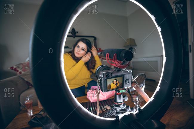 Beautiful female vlogger applying mascara at home