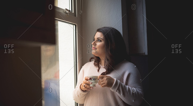 Beautiful female having coffee at home