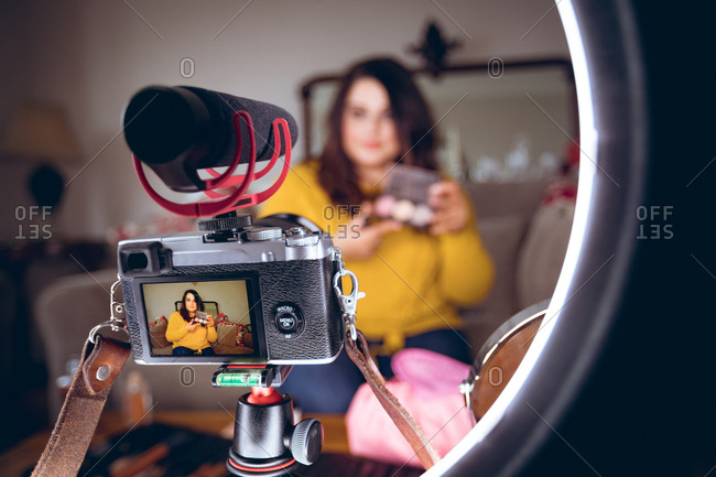Female video blogger recording video vlog at home