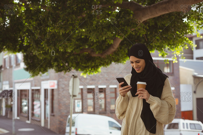 Smiling hijab woman reviewing photos on mobile phone at street