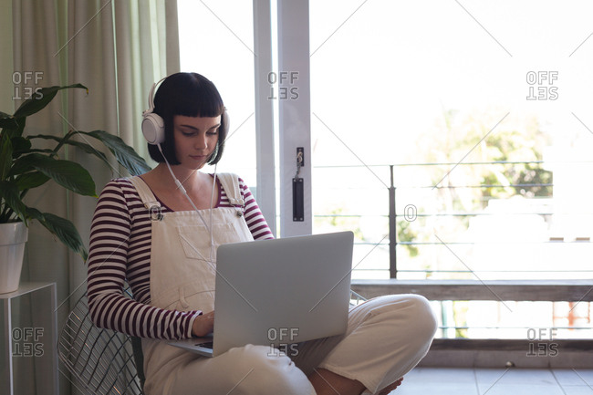 Young woman with headphones using laptop at home