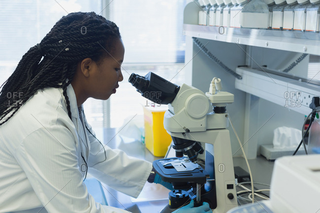 Female researcher analyzing samples with microscope in the laboratory