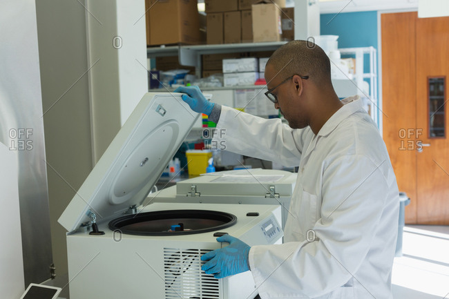 Scientist using a machine for experiment in lab