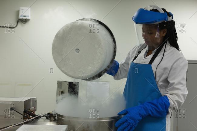Female scientist opening lid of machine in lab