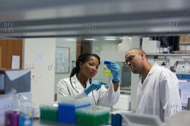 Scientists checking a solution in bottle in lab