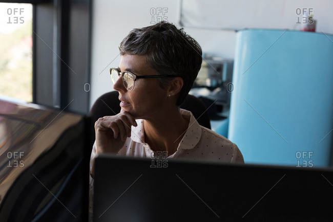 Thoughtful mature businesswoman looking away in the office