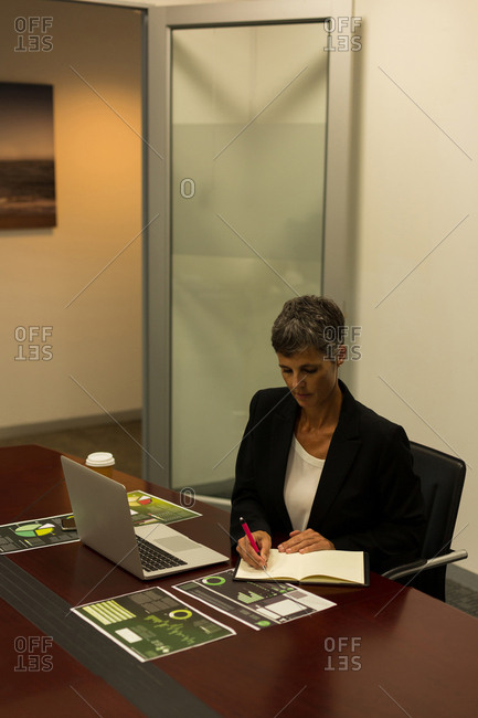 Mature businesswoman writing in diary at office desk