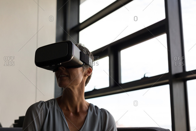 Mature businesswoman using virtual reality headset in the office