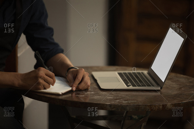 Close-up of businessman writing on diary in the cafe