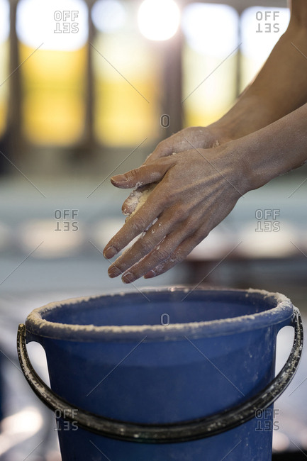 Close-up of sportswoman using chalk powder at fitness studio