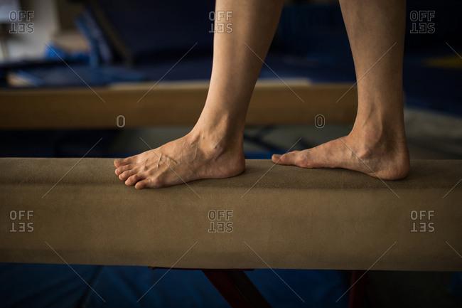 Sportswoman balancing on wooden bar at fitness studio
