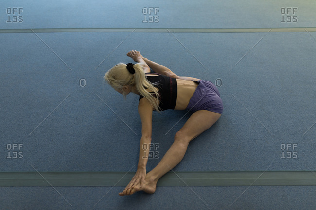 Sportswoman performing stretching exercise at fitness studio