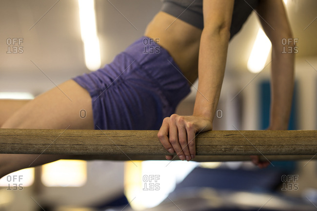 Mid section of sportswoman exercising on gym bar at fitness studio