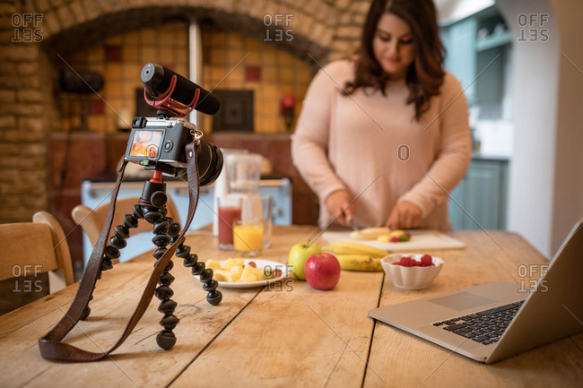Female vlogger cutting fruit on chopping board at home