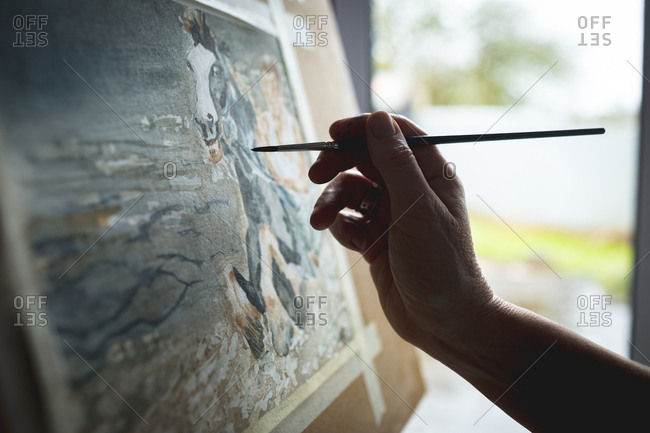 Hand of female artist painting picture on canvas at home