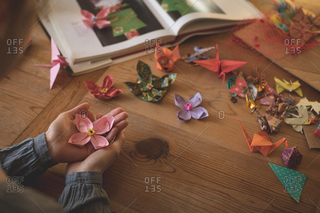Woman showing origami in hand at home