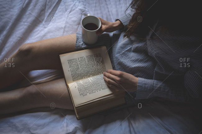 Woman with coffee reading a book on bed at home