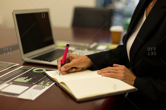Mid section of mature businesswoman writing in diary on desk at office