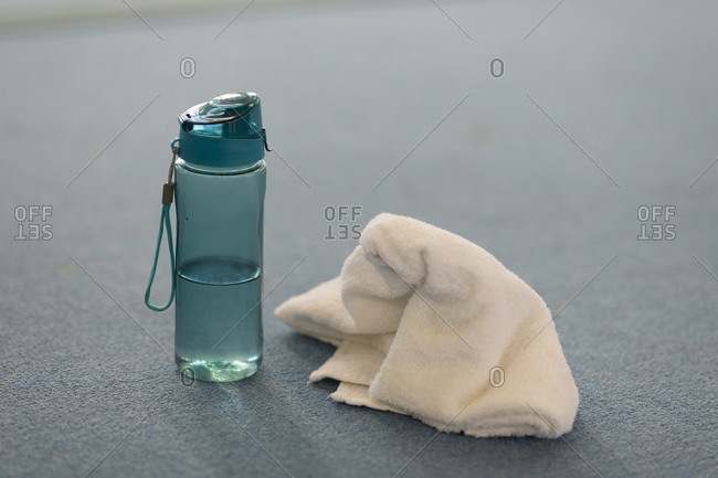 Close-up of water sipper with towel at fitness studio