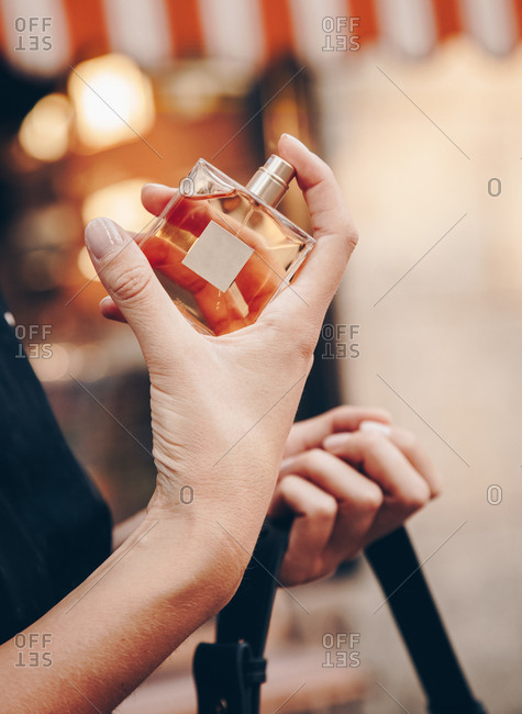 Detail of a hand holding an expensive perfume bottle outdoors