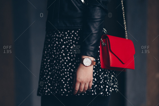 Street style fashion detail, close-up of a woman wearing a leather jacket, red purse and an analog wrist watch