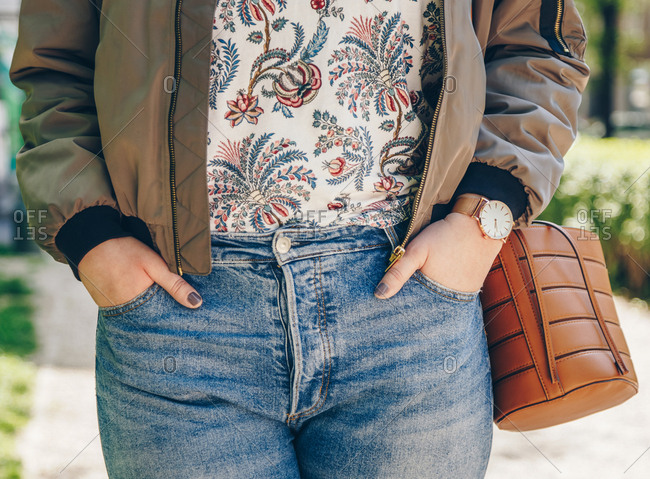 Street style fashion detail, close-up of a woman wearing a rose gold watch, bomber jacket, blue jeans and brown leather bucket bag