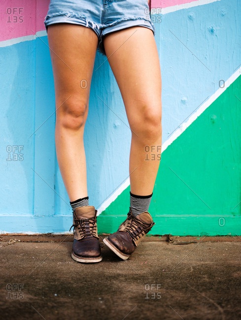 Bare legs of girl standing against colorful wall