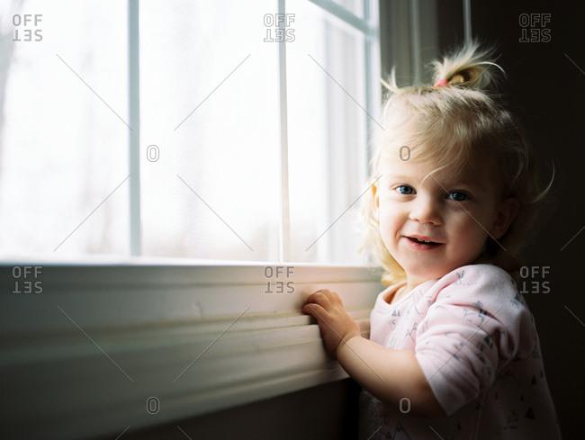 Portrait of little girl standing by window
