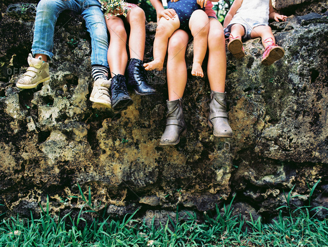Legs of five kids from toddler to tween sitting side by side on a boulder