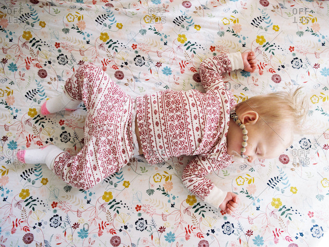 Looking down on little baby sprawled asleep on patterned bed clothes