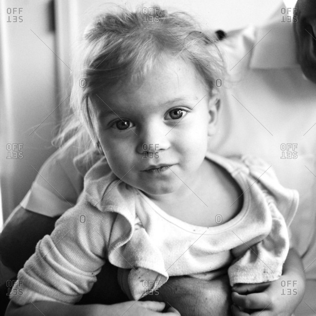 Portrait of little girl as she is being held by dad