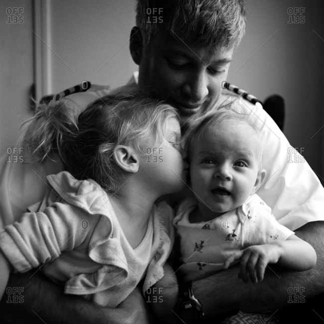 Young girl kissing baby brother as dad holds them both in his arms