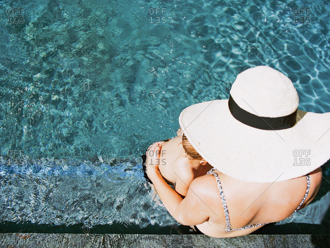 High angle view of mother wearing large sun hat holding child at side of pool