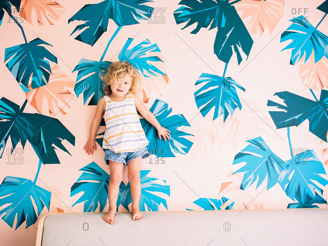 Little girl standing on bed against colorful wallpaper with palm leaf motif