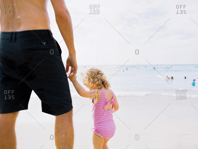 Rearview of little girl holding hands with father at beach