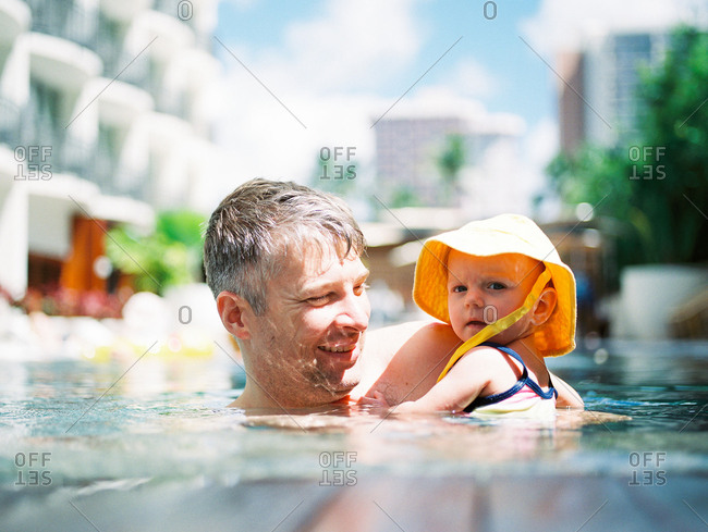 Happy dad holding baby daughter in swimming pool