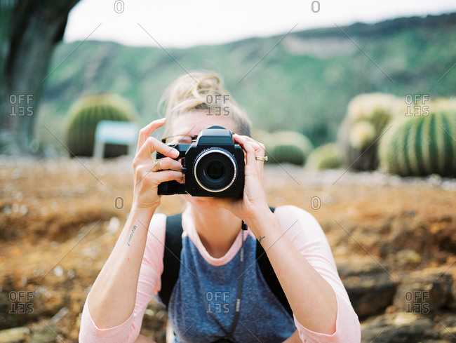 Portrait of woman with camera covering her face