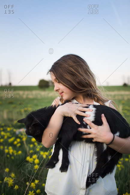 Portrait of young girl holding baby goat in her arms