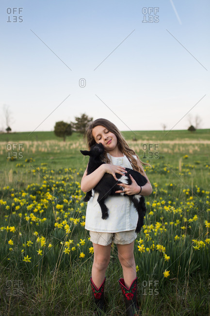 Portrait of young girl holding and being licked by baby goat
