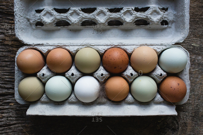 Top down view of carton of fresh farm yard eggs of varying colors