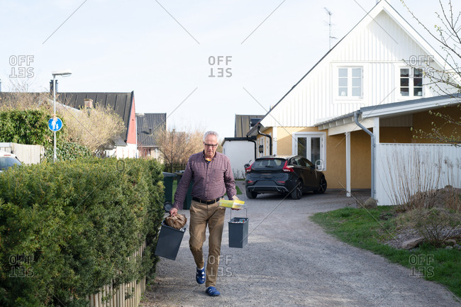 Man carrying household waste outside home