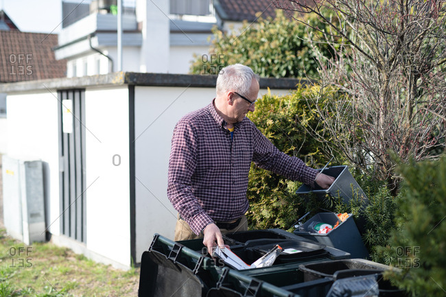 Elderly man sorting and placing cardboard waste in correct container in yard